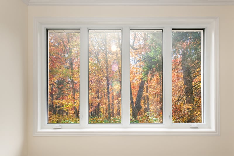 Large four pane storm windows looking on colorful fall forest