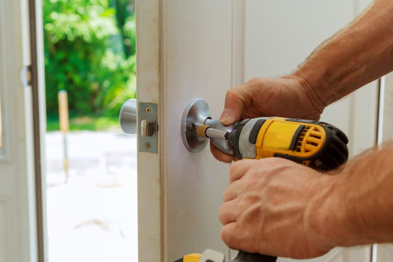 Man using drill to install new door
