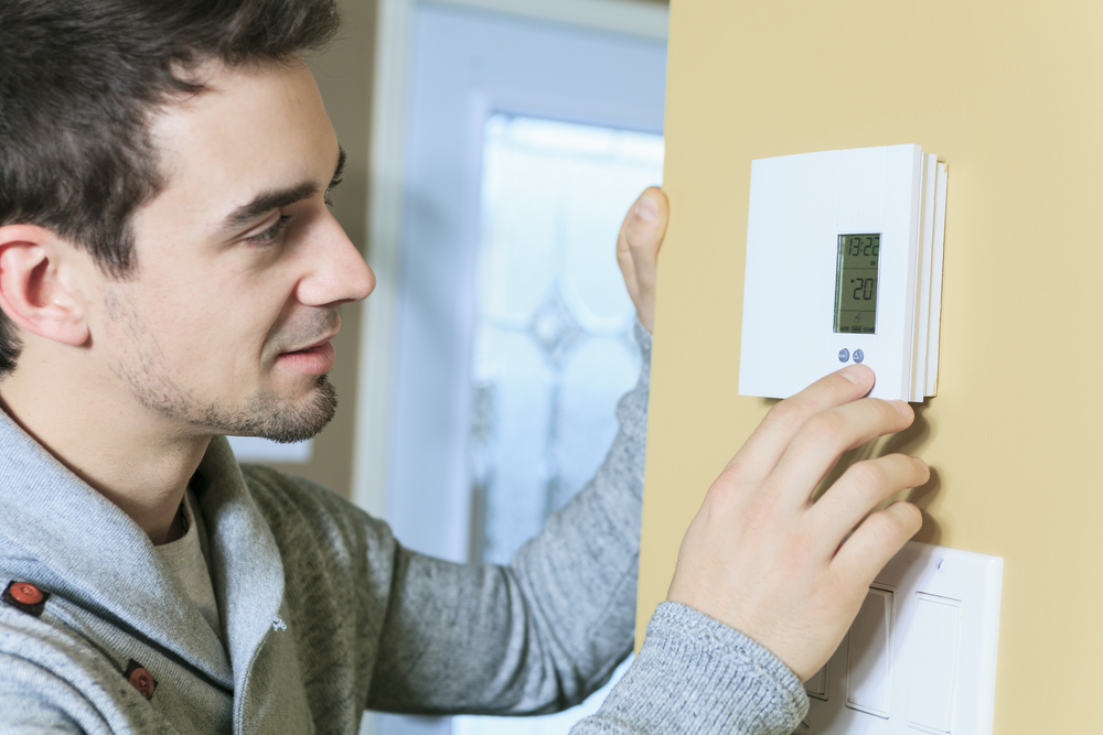 Man controlling thermostat in house